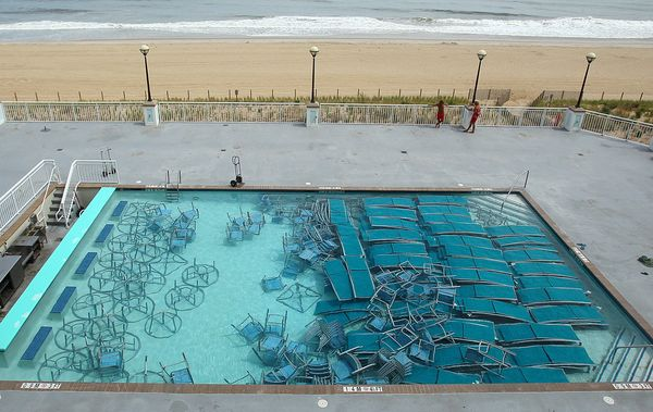 a swimming pool filled with lounge chairs and tables in preparation for a hurricane